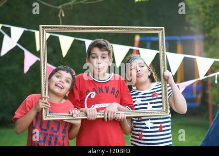 Three children looking through picture frame, sticking out tongues - Stock Photo