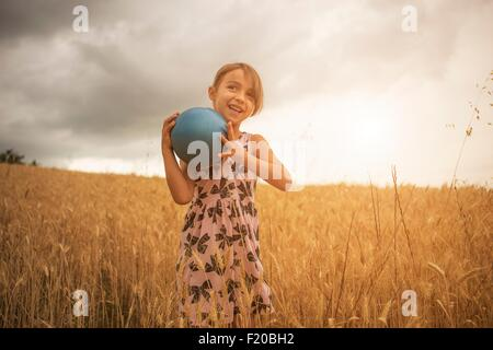 Girl holding blue ball in wheat field - Stock Photo
