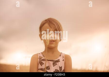 Portrait of girl with ear of wheat in front of her face in wheat field - Stock Photo