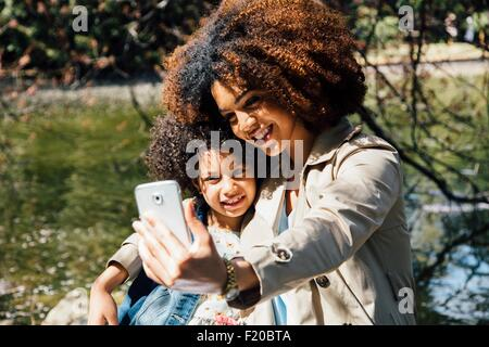 Mother with arm around daughter using smartphone to take selfie - Stock Photo