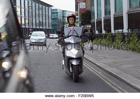 Motor scooter rider, undertaking taxi driver training 'the knowledge', on the move in London - Stock Photo