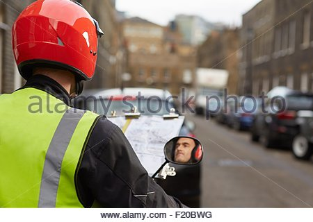 Motor scooter rider, undertaking taxi driver training 'the knowledge', reflected in wing mirror - Stock Photo