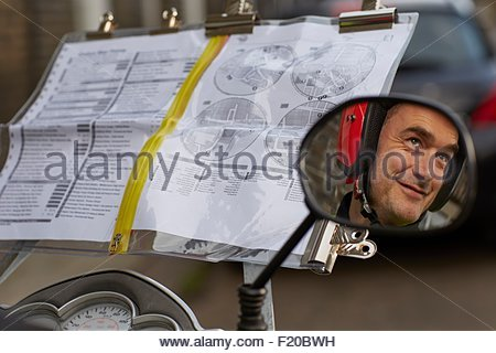 Reflection of motor scooter rider, undertaking taxi driver training 'the knowledge' in wing mirror - Stock Photo
