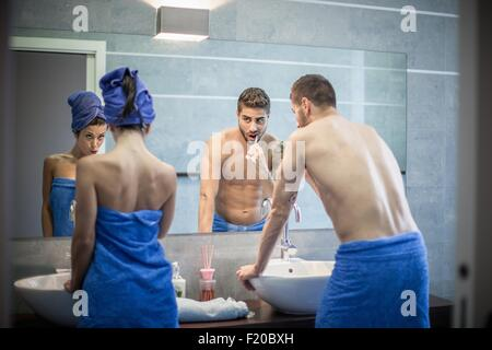 Rear view of young couple brushing teeth in bathroom mirror - Stock Photo