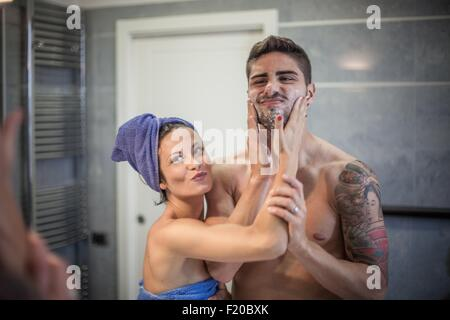 Bathroom mirror image of young woman applying shaving lotion to boyfriends cheeks - Stock Photo