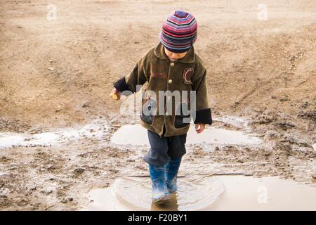 Male toddler wearing rubber boots paddling in puddle - Stock Photo