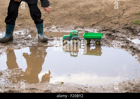 Legs of male toddler wearing rubber boots playing with toy tractor in muddy puddle - Stock Photo