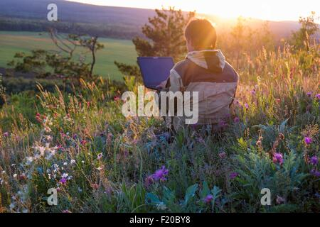 Mid adult man sitting in wildflower meadow using laptop - Stock Photo
