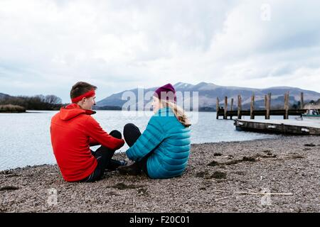 Young couple hiking, sitting by waters edge, Derwent Water, Keswick, Lake District, Cumbria, United Kingdom - Stock Photo