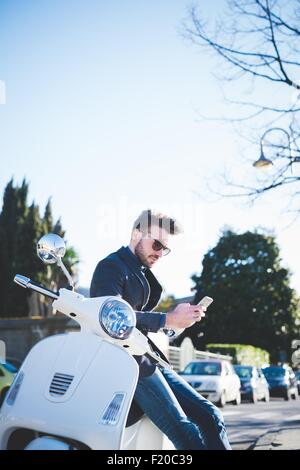 Stylish young man reading smartphone texts on moped - Stock Photo
