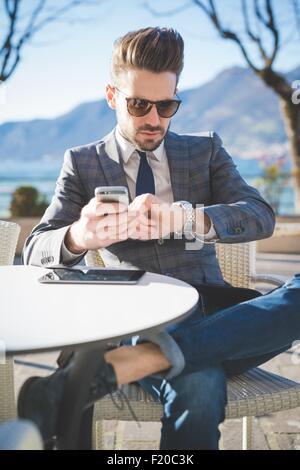 Businessman checking the time at lakeside cafe, Rovato, Brescia, Italy - Stock Photo
