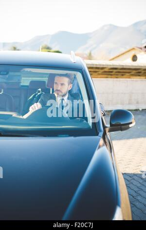 Young businessman sitting in car - Stock Photo