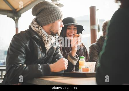 Four young adult friends chatting and eating doughnuts at sidewalk cafe - Stock Photo