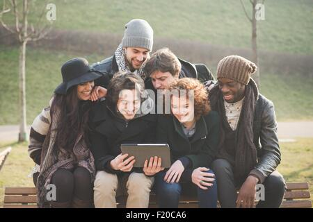 Six young adult friends using digital tablet on park bench - Stock Photo