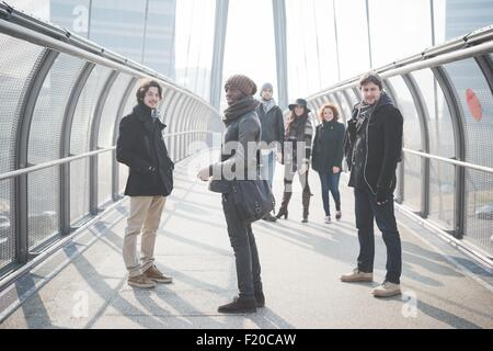 Portrait of six young adult friends on footbridge - Stock Photo
