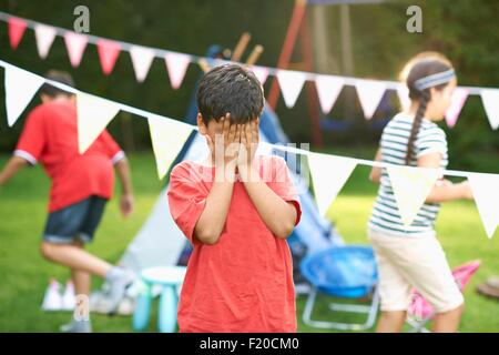 Boy covering his eyes for hide and seek with brother and sister in garden - Stock Photo