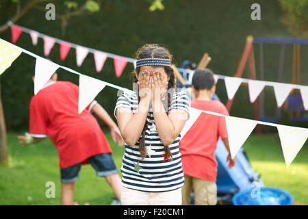 Girl covering her eyes for hide and seek with brothers in garden - Stock Photo