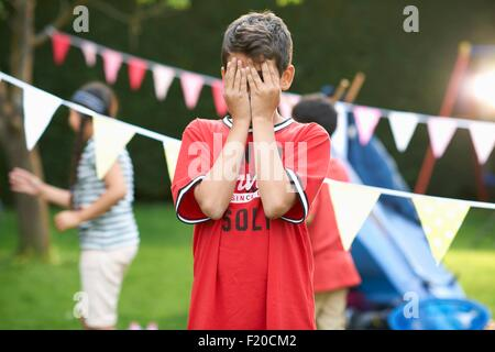 Boy covering his eyes for hide and seek with sister and brother in garden - Stock Photo