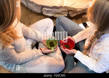 High angle view of two young women drinking herbal tea in front of fireplace - Stock Photo