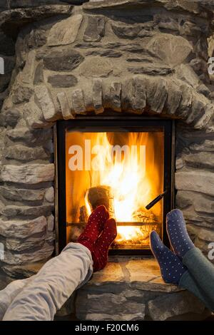 Cropped shot of two young women with feet up in front of fireplace - Stock Photo