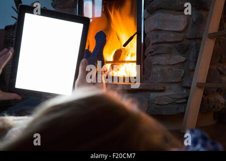 Young woman using digital tablet with feet up in front of fireplace - Stock Photo