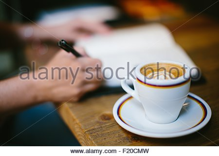 Coffee cup on table and womans hands writing in notebook - Stock Photo