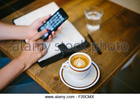 High angle view of coffee cup on table and womans hands using smartphone - Stock Photo