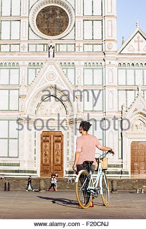 Rear view of mid adult woman holding bicycle looking at Basilica of Santa Croce, Florence, Italy - Stock Photo