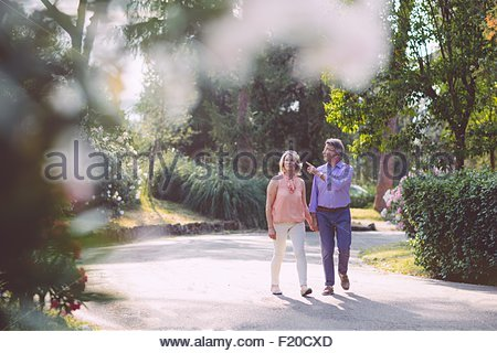 Senior couple outdoors, walking hand in hand, looking at view - Stock Photo