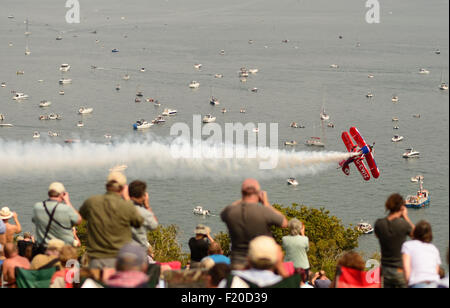 Spectators watching Rich Goodwin's Muscle biplane performing aerobatic fly-past at Dawlish airshow. - Stock Photo