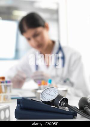 Female doctor examining test tube at desk in clinic - Stock Photo