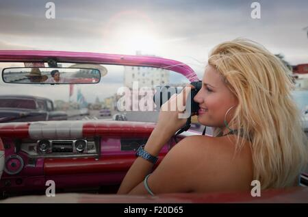 Young woman taking pictures from a vintage car on the Havana' Malecon, Cuba - Stock Photo