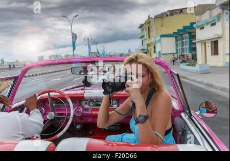 Young woman photographing from a vintage car on the Havana' Malecon, Cuba - Stock Photo