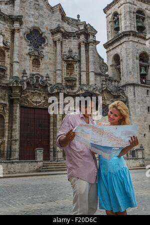 Young couple with map in the Plaza de la Cathedral of Havana, Cuba - Stock Photo
