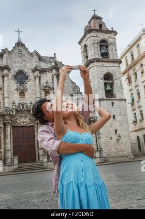 Young couple taking selfie with smartphone in the Plaza de la Cathedral of Havana, Cuba - Stock Photo