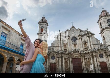 Young couple taking smartphone selfie in the Plaza de la Cathedral of Havana, Cuba - Stock Photo