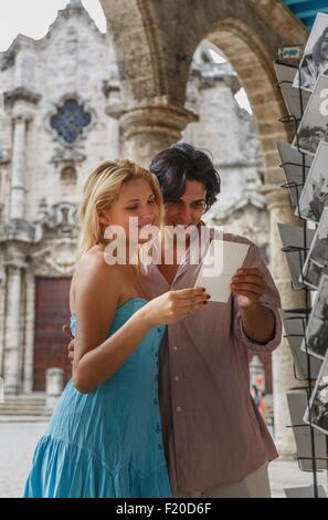 Young couple looking at postcards in the Plaza de la Cathedral of Havana, Cuba - Stock Photo