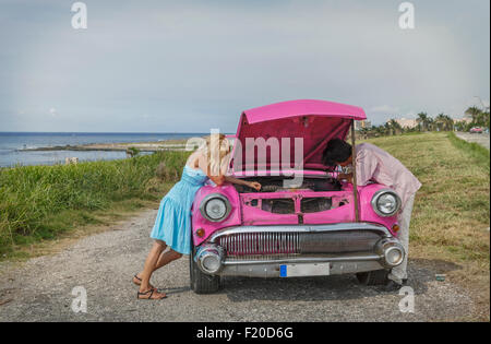 Young couple trying to fix a vintage convertible at coast, Havana, Cuba - Stock Photo