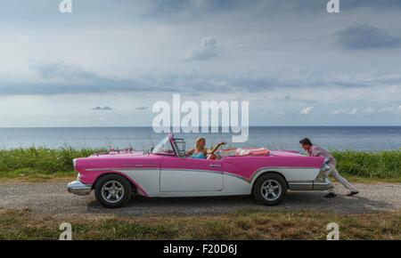 Young man pushing vintage convertible at coast whilst girlfriend drives, Havana, Cuba - Stock Photo