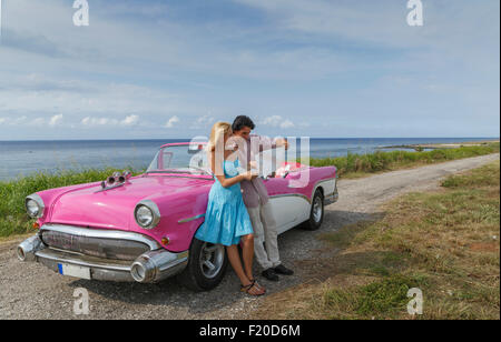 Young couple looking at map beside vintage convertible at coast, Havana, Cuba - Stock Photo