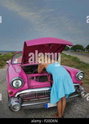 Young woman trying to fix a vintage convertible at coast, Havana, Cuba - Stock Photo