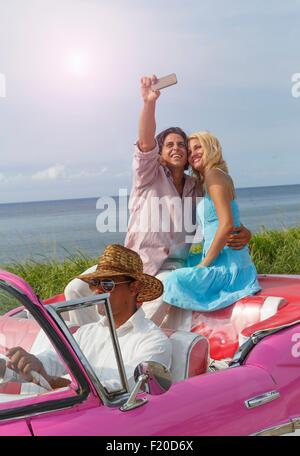 Young couple taking smartphone selfie in vintage convertible, Havana, Cuba - Stock Photo