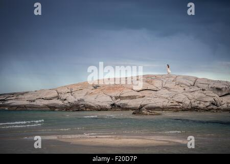 Distant view of young woman strolling on rock formation at coast, Costa Rei, Sardinia, Italy - Stock Photo