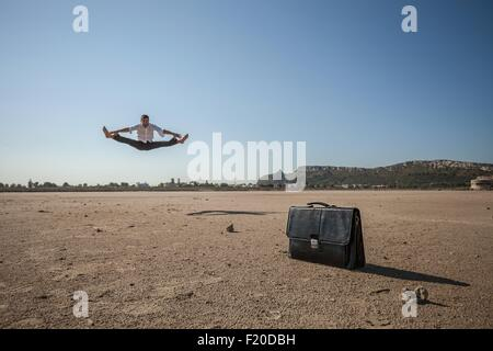 Mid adult businessman jumping mid air at beach - Stock Photo