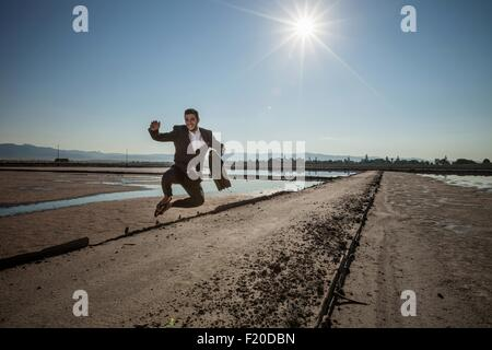 Mid adult businessman carrying briefcase jumping mid air at beach - Stock Photo