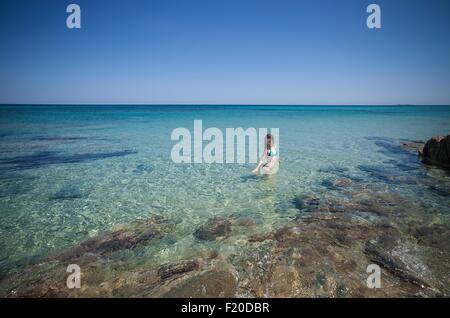 Young woman wearing bikini wading in sea, Cagliari, Sardinia, Italy - Stock Photo