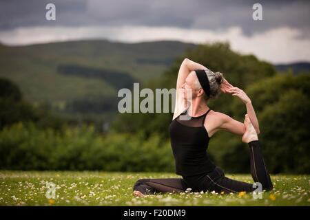 Mature woman doing splits practicing yoga in field - Stock Photo