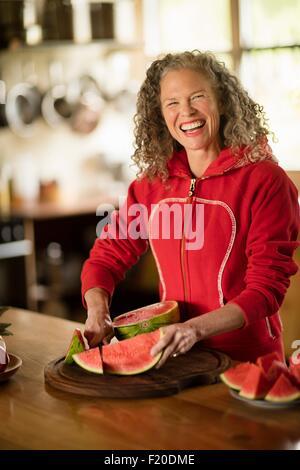 Portrait of mature woman slicing watermelon in kitchen - Stock Photo