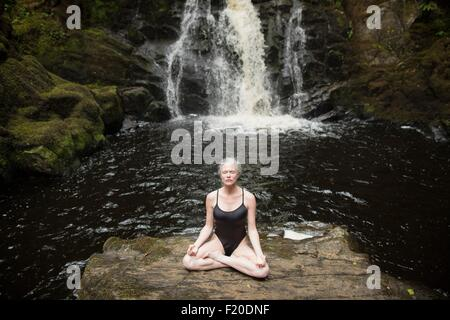 Mature woman practicing lotus pose in front of waterfall - Stock Photo