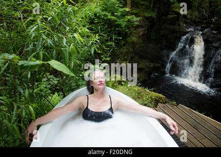 Mature woman relaxing in bubble bath in front of waterfall at eco retreat - Stock Photo